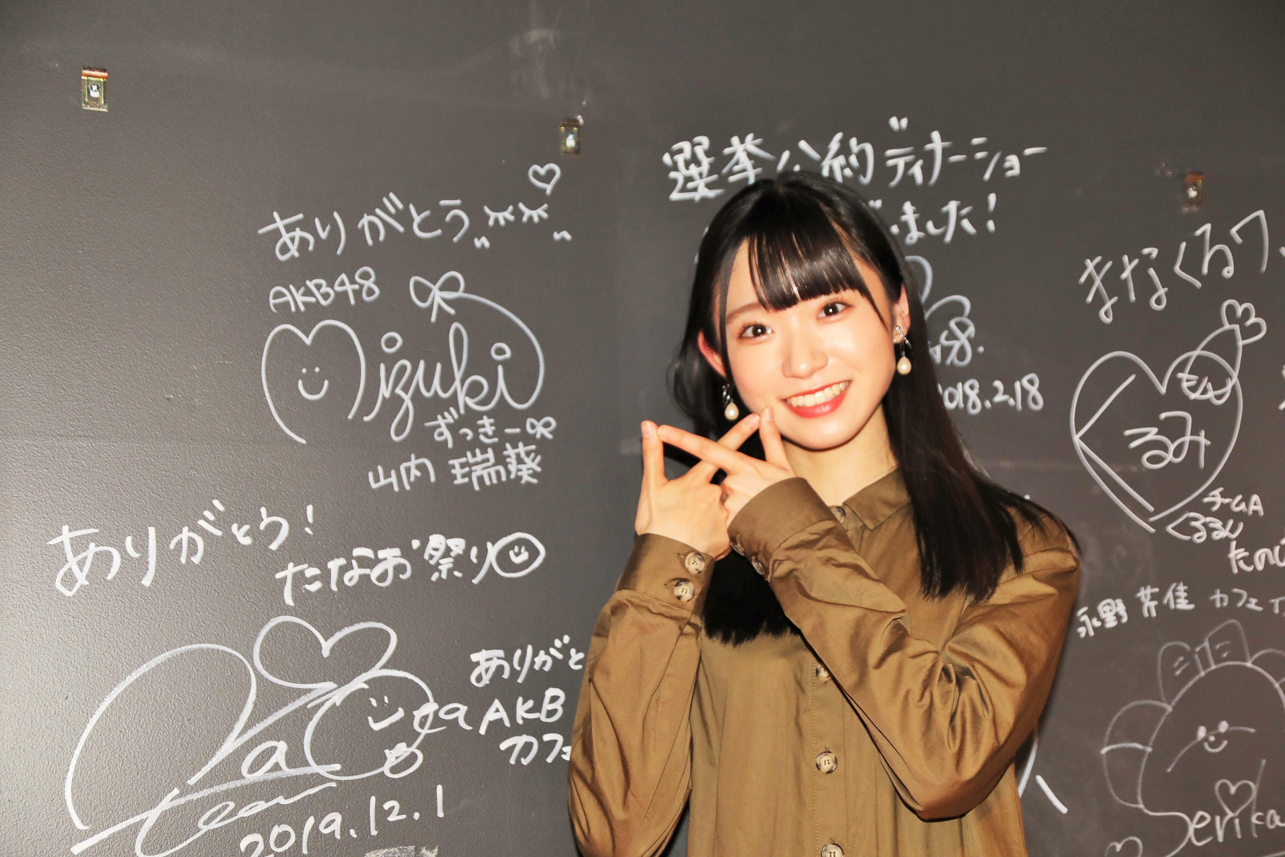 カフェの壁にサインをした山内瑞葵