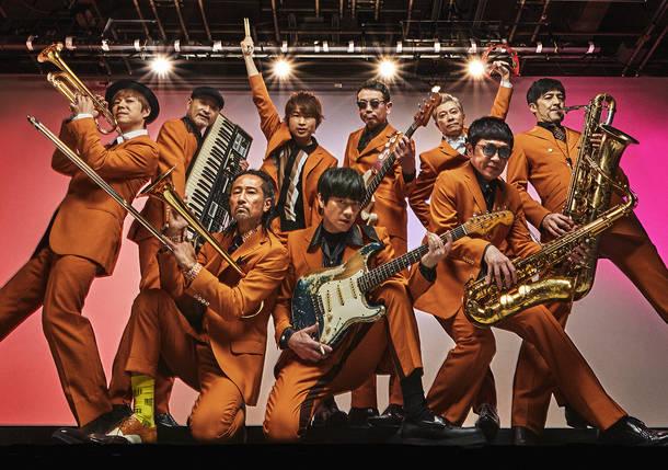 写真左から時計回りに、NARGO(Trumpet)、沖 祐市(Key)、茂木欣一(Dr)、川上つよし(Ba)、大森はじめ(Percussion)、谷中 敦(Baritone sax)、GAMO(Tenor sax)、加藤隆志(Gu)、北原雅彦(Trombone)