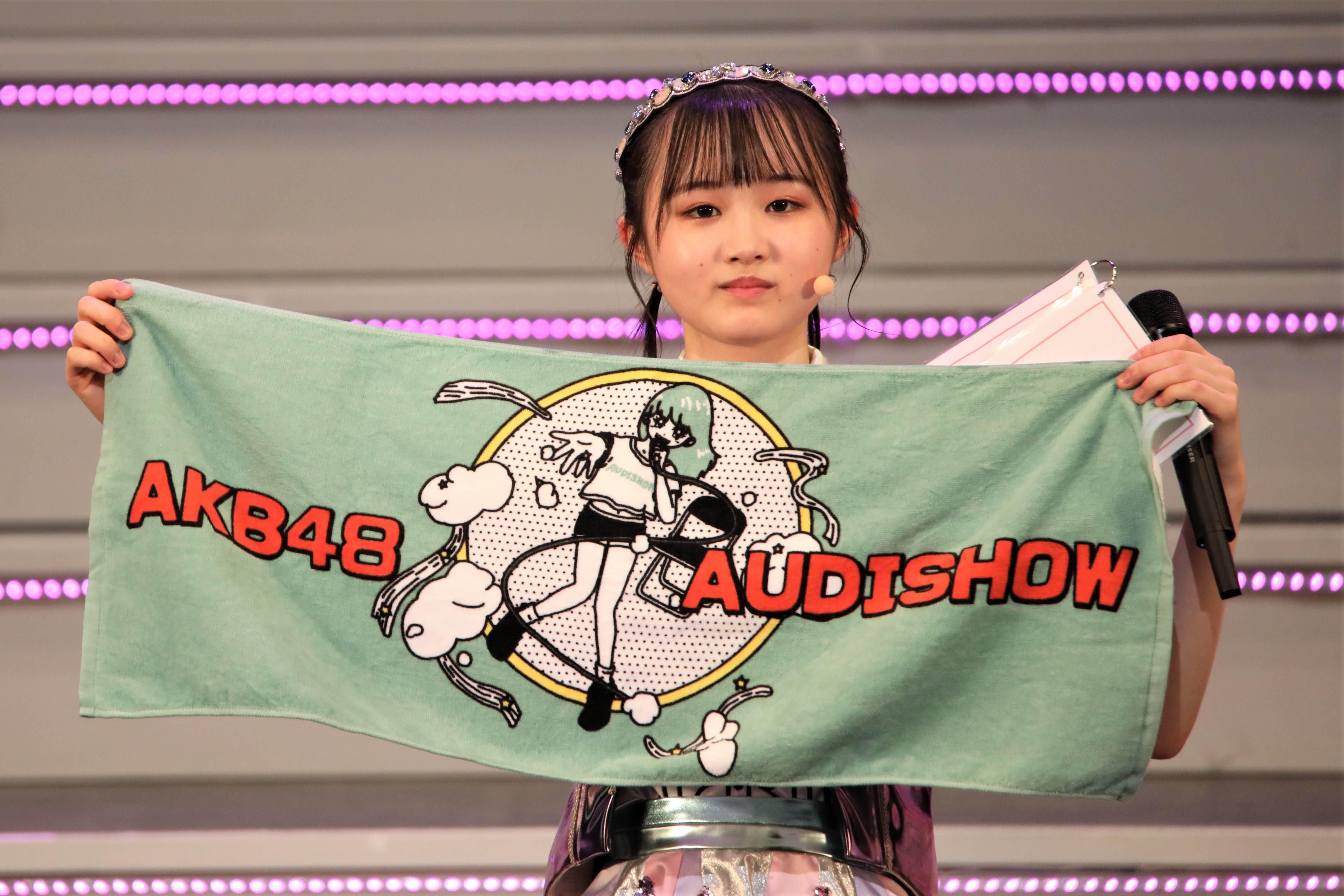 今回のコンサートを記念したグッズを紹介する齋藤陽菜  ©AKB48 THE AUDISHOW製作委員会  無断アップロード及び転送は一切禁止です。