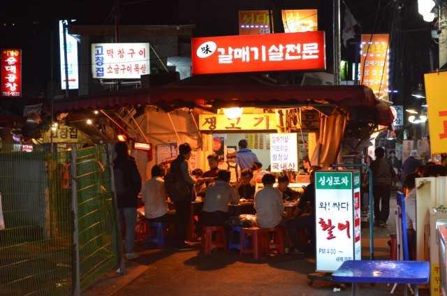 ソウルでもっとも絵になる酒場のひとつ『味カルメギサル専門』。店の入口に向かって左手の道沿いにもテーブルが並ぶが、冬場はここに半透明のビニールカーテンがかかる